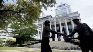 Dua polisi bersalaman tatkala berjumpa di tempat penugasan mereka di Gedung Mahkamah Konstitusi Jakarta, Selasa (5/8/2014)