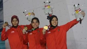 Tim beregu putri panjat tebing Indonesia mempertontonkan medali emas yang diraihnya setelah mengalahkan Tim China, di final yang digelar di SC Sport Climbing, Palembang, Senin (27/8) malam. (Foto: IST)