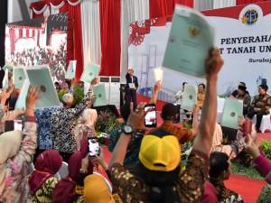 Presiden Jokowi menghitung sertfikat yang dipegang masyarakat dalam acara penyerahan 5.000 sertifikat untuk warga Jatim, di Jatim Expo, Surabaya, Kamis (6/9) siang. (Foto: BPMI Setpres)