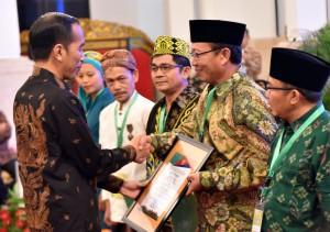 Presiden Jokowi menyerahkan sertifikat tanah perhutanan sosial dalam acara Rembug Nasional Performa Agraria, di Istana Negara, Jakarta, Kamis (20/9) pagi. (Foto: Rahmat/humas)