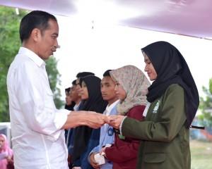 Presiden menyerahkan beasiswa di halaman luar Bandar Udara Internasional Zainuddin Abdul Madjid, Kabupaten Lombok Tengah, Kamis (18/10). (Foto: BPMI)