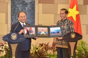 Presiden Jokowi berfoto bersama sembari menunjukkan foto-foto dokumentasi keduanya, di BNDCC, Nusa Dua, Bali, Jumat (12/10) pagi. (Foto: JAY/Humas)