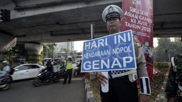 Seorang petugas kepolisian dengan sabar memperlihatkan papan sosiliasasi kawasan ganjil genap.