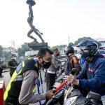Anggota Polisi memeriksa identitas pengendara sepeda motor saat berlangsungnya Pemberlakuan Pembatasan Kegiatan Masyarakat (PPKM) Darurat di kawasan Bundaran Senayan, Jakarta, (Antara)