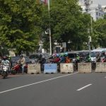 Sejumlah kendaraan bermotor menerobos bagian jalan yang tidak tertutup beton di posko penyekatan tanpa penjagaan petugas di Jalan Salemba Raya, Jakarta Pusat, Senin (5/7/2021). Foto: Antara/Aditya Pradana Putra/wsj.